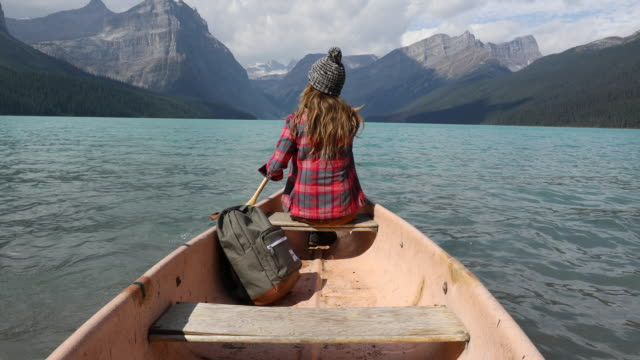 a young woman paddling a canoe across a high alpine lake. - andare in canoa video stock e b–roll
