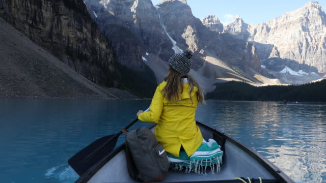 A young woman paddling a canoe across the turquoise blue waters of Moraine Lake.