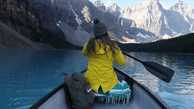 a young woman paddling a canoe across the turquoise blue waters of moraine lake. - canoe stock videos & royalty-free footage
