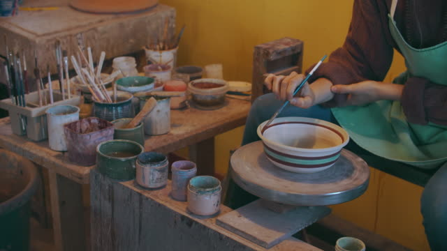 young woman painting a bowl in her ceramics studio - pottery stock videos & royalty-free footage