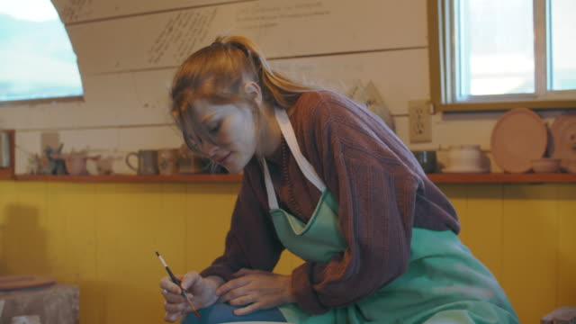 tu young woman painting a bowl in her ceramics studio - pottery stock videos & royalty-free footage