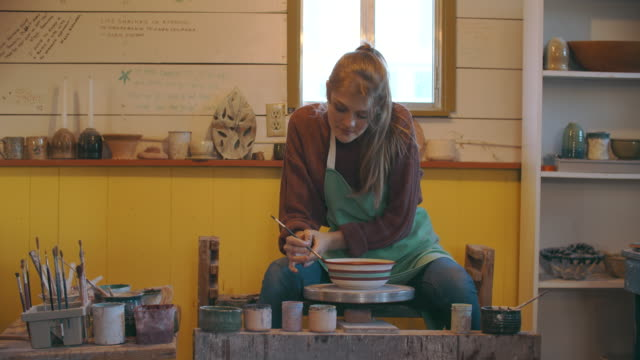 young woman painting a bowl in her studio - art studio stock videos & royalty-free footage