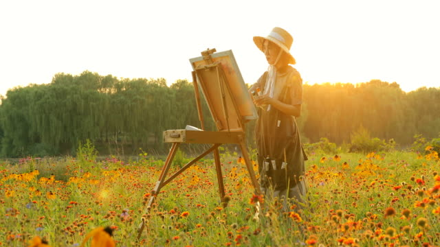 young woman painting at sunset - paint tube stock videos and b-roll footage