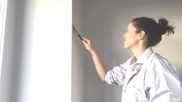 Young woman painting city apartment