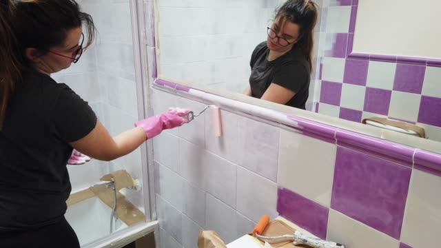 young woman painting her bathroom tiles white - matte finish stock videos & royalty-free footage