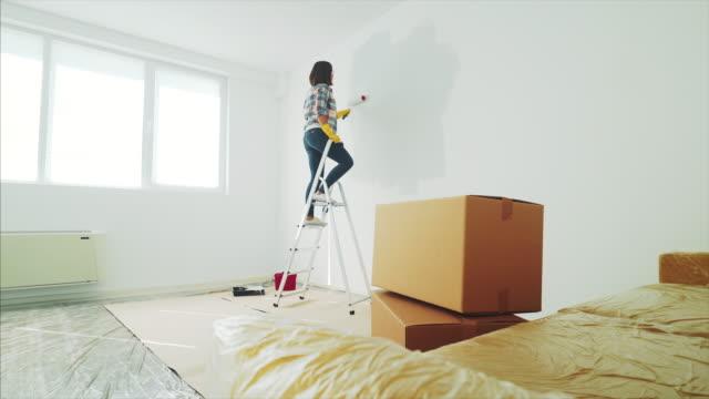 vídeos y material grabado en eventos de stock de joven pintando su nuevo apartamento. - reforma
