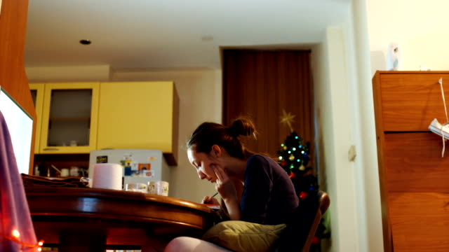 young woman painting in living room decorated with christmas tree - oil paint stock videos and b-roll footage