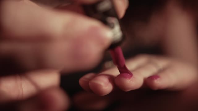 young woman painting nails red, close up - red nail polish stock videos and b-roll footage
