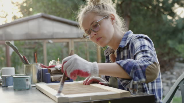 young woman painting old furniture - bricolage video stock e b–roll
