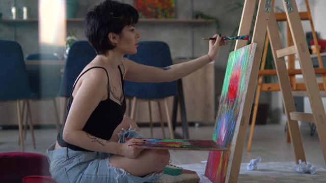 young woman painting on canvas in home studio - short hair stock videos & royalty-free footage