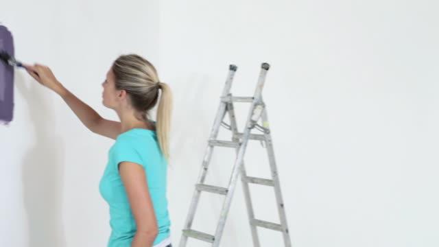 vídeos y material grabado en eventos de stock de young woman painting purple paint on wall - sólo mujeres jóvenes