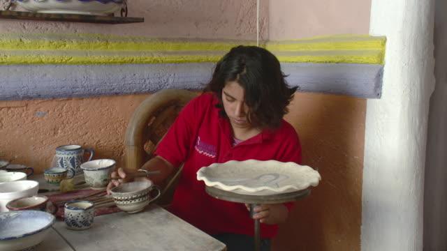vídeos de stock, filmes e b-roll de ms young woman painting talavera pottery / puebla, mexico - camisa pólo