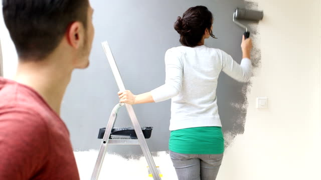 ms young woman painting wall with paint roller - paint roller stock videos & royalty-free footage