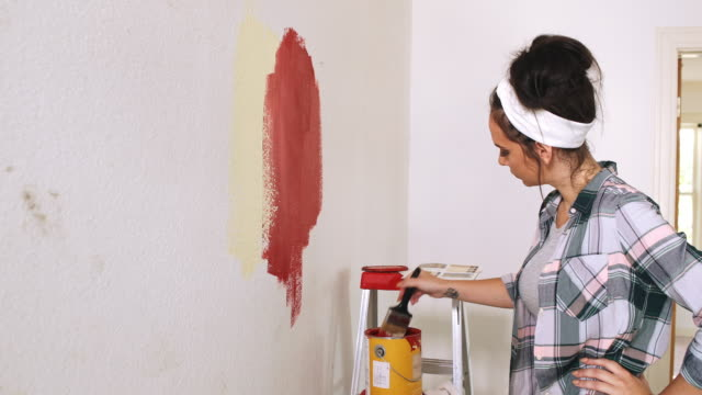 A young woman paints a color swatch onto a wall.