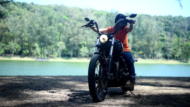 young woman parking a chopper beside the lake. - montare video stock e b–roll