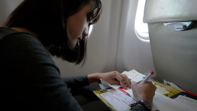 young woman passenger write immigration card in airplane - pen stock videos & royalty-free footage