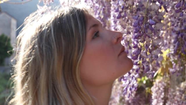 Junge Frau überfällt Glyzierblüten bei Sonnenaufgang