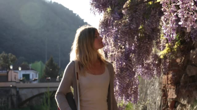 young woman passes wisteria blossoms at sunrise - sensory perception stock videos & royalty-free footage
