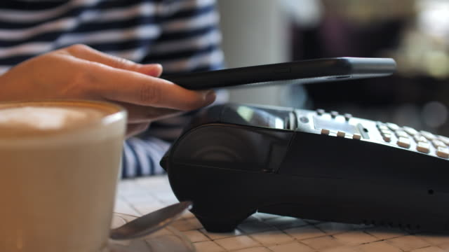 young woman paying by mobile phone at cafe, contectless payment - contactless payment stock videos & royalty-free footage