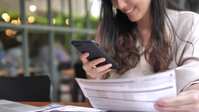young woman paying online bills on smart phone - electronic banking stock videos and b-roll footage
