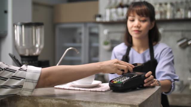 vidéos et rushes de jeune femme payer via téléphone intelligent, slow motion, dolly tourné - payer