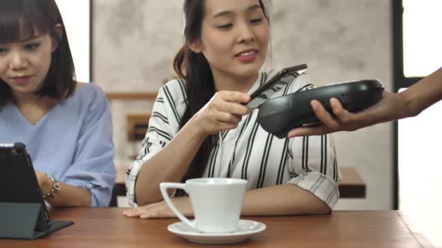 Young woman paying via smart phone