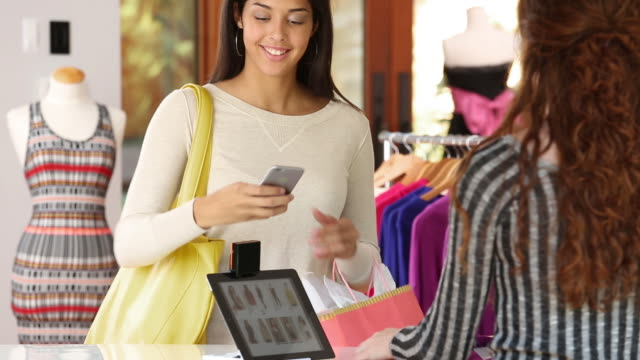 young woman paying with her smart phone at a retail store - checkout stock videos & royalty-free footage