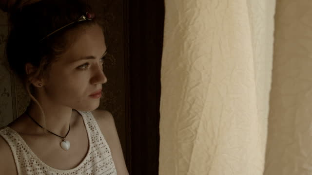 young woman peeking out of the window. - peeking stock videos & royalty-free footage