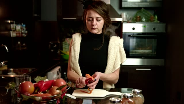 young woman peeling a carrot on the kitchen counter - peeling food stock videos & royalty-free footage