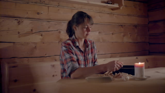young woman peeling garlic at a table in a wooden cabin - peel stock videos & royalty-free footage