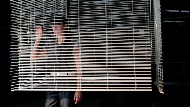 young woman peering though venetian blind - peeking stock videos & royalty-free footage
