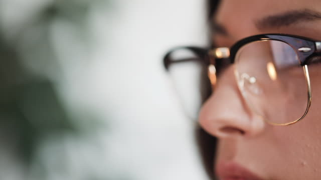 young woman pensive at her computer screen - reading glasses stock videos & royalty-free footage