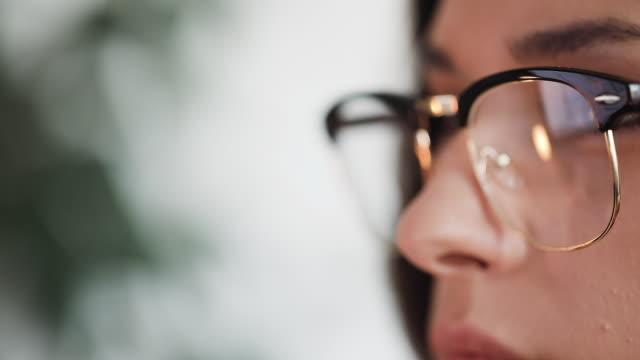 vídeos de stock, filmes e b-roll de mulher nova pensativa em sua tela de computador - óculos