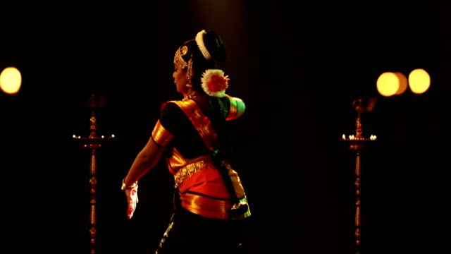 vidéos et rushes de ms young woman performing bharatanatyam dance on stage / india - cadrage aux genoux