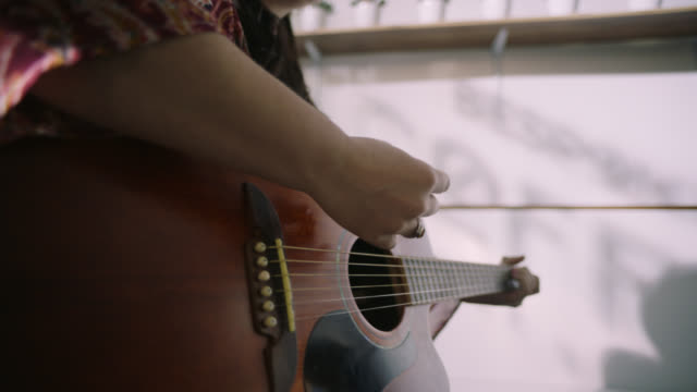 Young woman performing in local coffee shop plays acoustic guitar and sings.