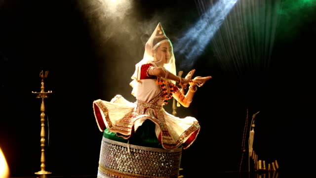 vidéos et rushes de ms young woman performing manipuri classical dance on stage / india - cadrage aux genoux