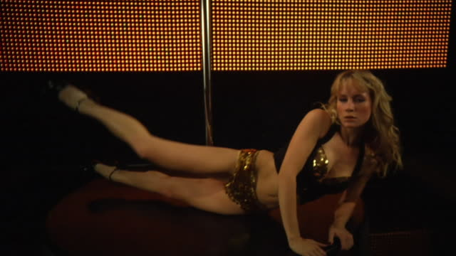WS TU TD SLO MO Young woman performing pole dance on stage / London, UK