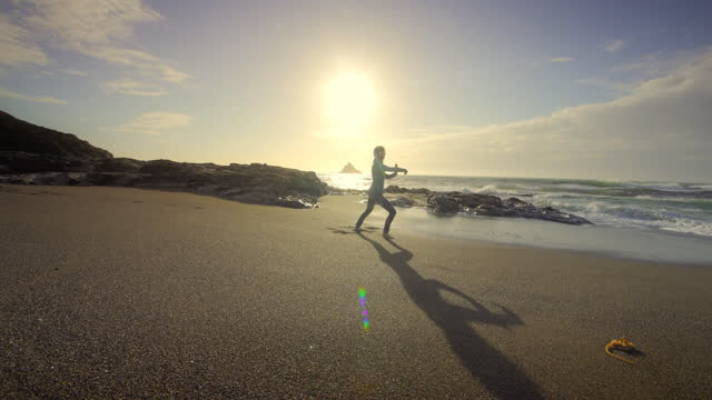 young woman performing tai chi on beach - relaxation stock videos & royalty-free footage
