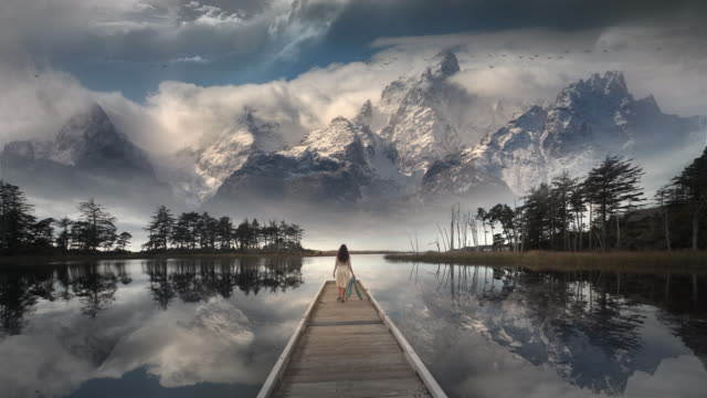 vidéos et rushes de young woman performing yoga on dock of lake reflecting rocky mountains, wyoming - idée