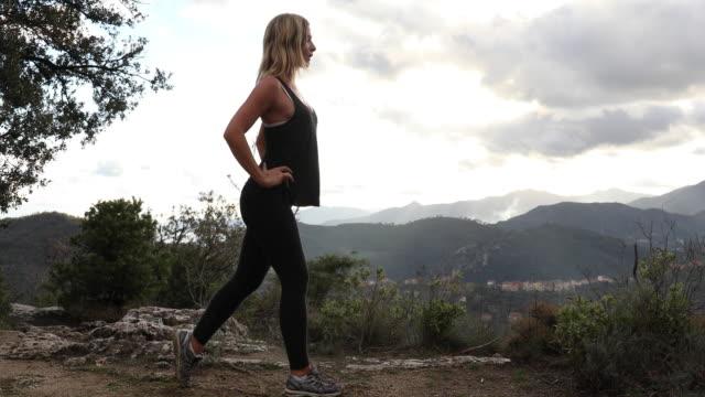 若い女性が高原に有酸素運動を実行します。 - 腰に手を当てる点の映像素材/bロール
