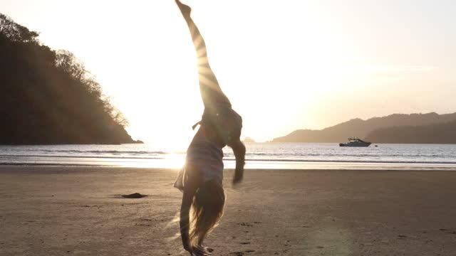 vídeos y material grabado en eventos de stock de young woman performs cartwheels along beach into surf - sólo mujeres jóvenes