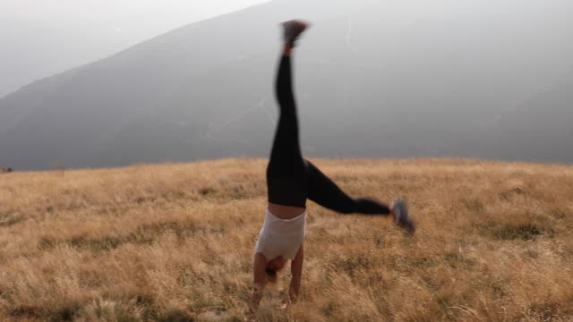 young woman performs cartwheels in grassy alpine meadow - cartwheel stock videos & royalty-free footage