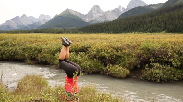 Young woman performs handstand in mountain meadow