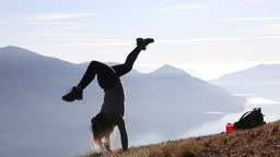 Young woman performs handstands on alpine slope