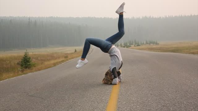 vídeos y material grabado en eventos de stock de young woman performs headstand on mountain road - sólo mujeres jóvenes