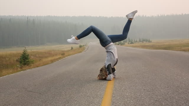 Young woman performs headstand on mountain road
