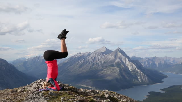 Young woman performs headstand on mountain summit