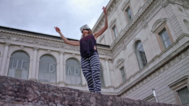 young woman performs modern dance in front of a very old building while wearing a VR head set (virtual-reallity)