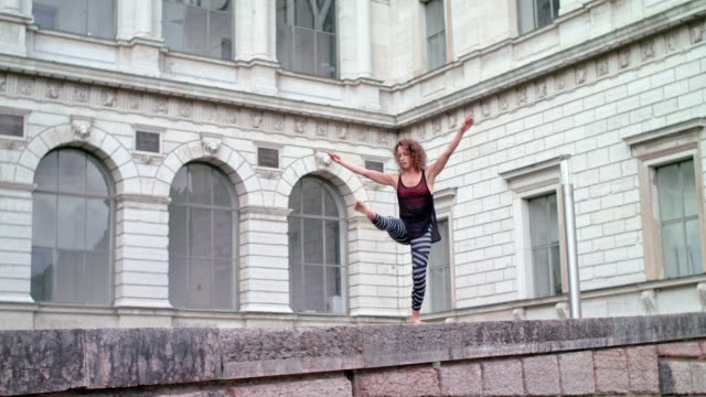 vídeos y material grabado en eventos de stock de young woman performs modern dance in front of a very old building / balancing on a wall - descalzo