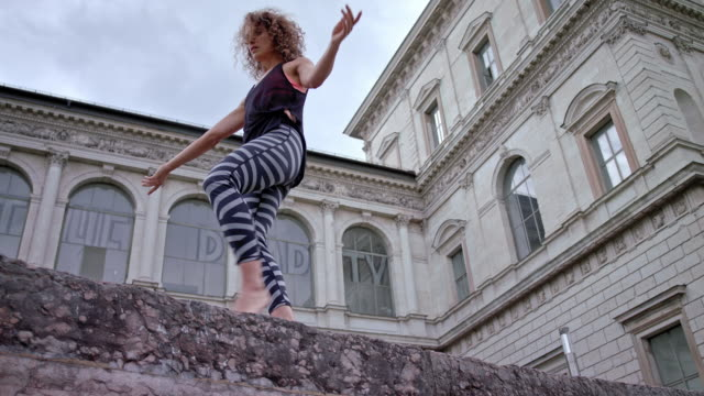 young woman performs modern dance in front of a very old building / balancing on a wall - 女性ダンサー点の映像素材/bロール